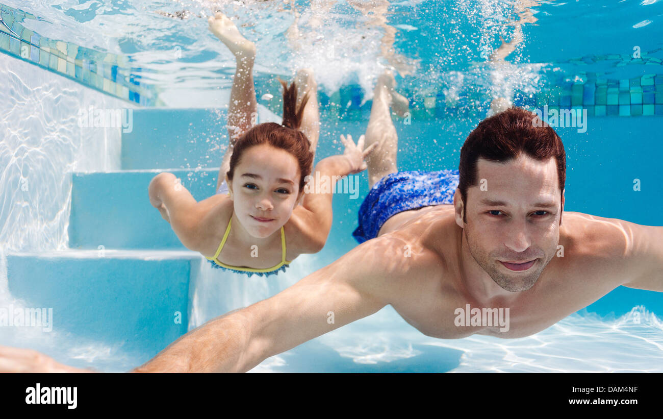 Father and daughter swimming in pool - Stock Image