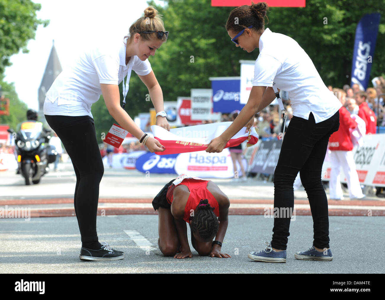 Ethiopian Fatuma Sado Dergo (M) kneels after her win in the Hamburg Marathon in Hamburg, Germany, 22 May 2011. More Stock Photo