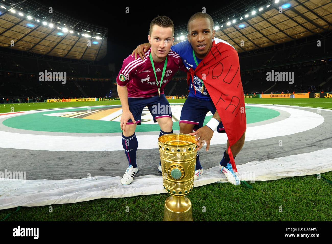 Schalke's Jefferson Farfan (R) and Alexander Baumjohann lean over the DFB cup after Schalke's 5:0 win in - Stock Image
