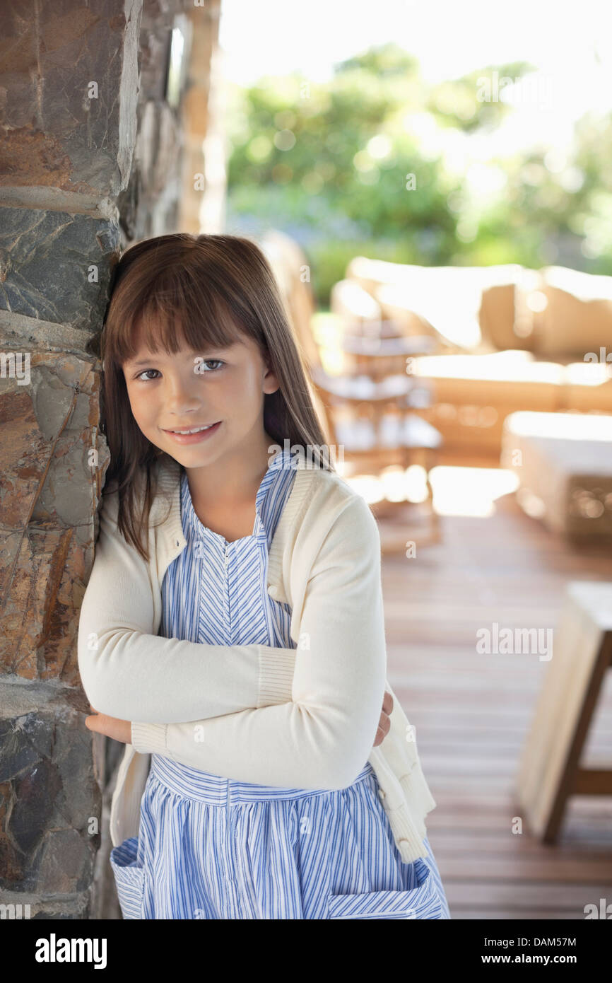 Girl leaning against stone wall - Stock Image