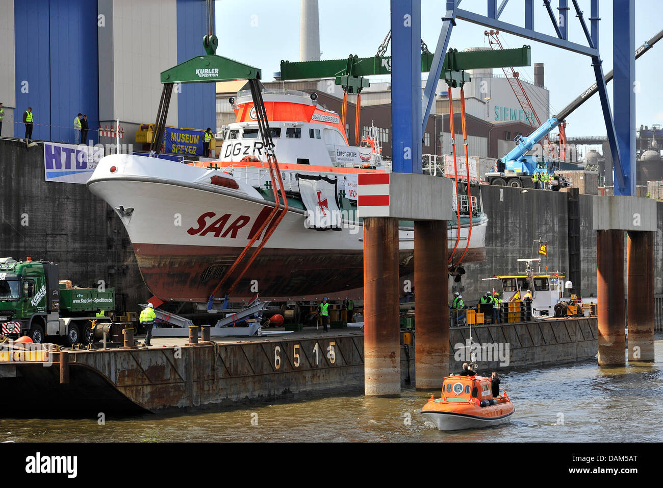 The sea rescue cruiser 'John T. Essberger' is loaded onto a floating pontoon by a special crane at the harbour - Stock Image