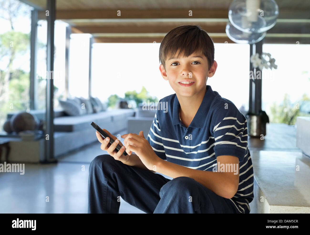 Boy using cell phone on steps - Stock Image