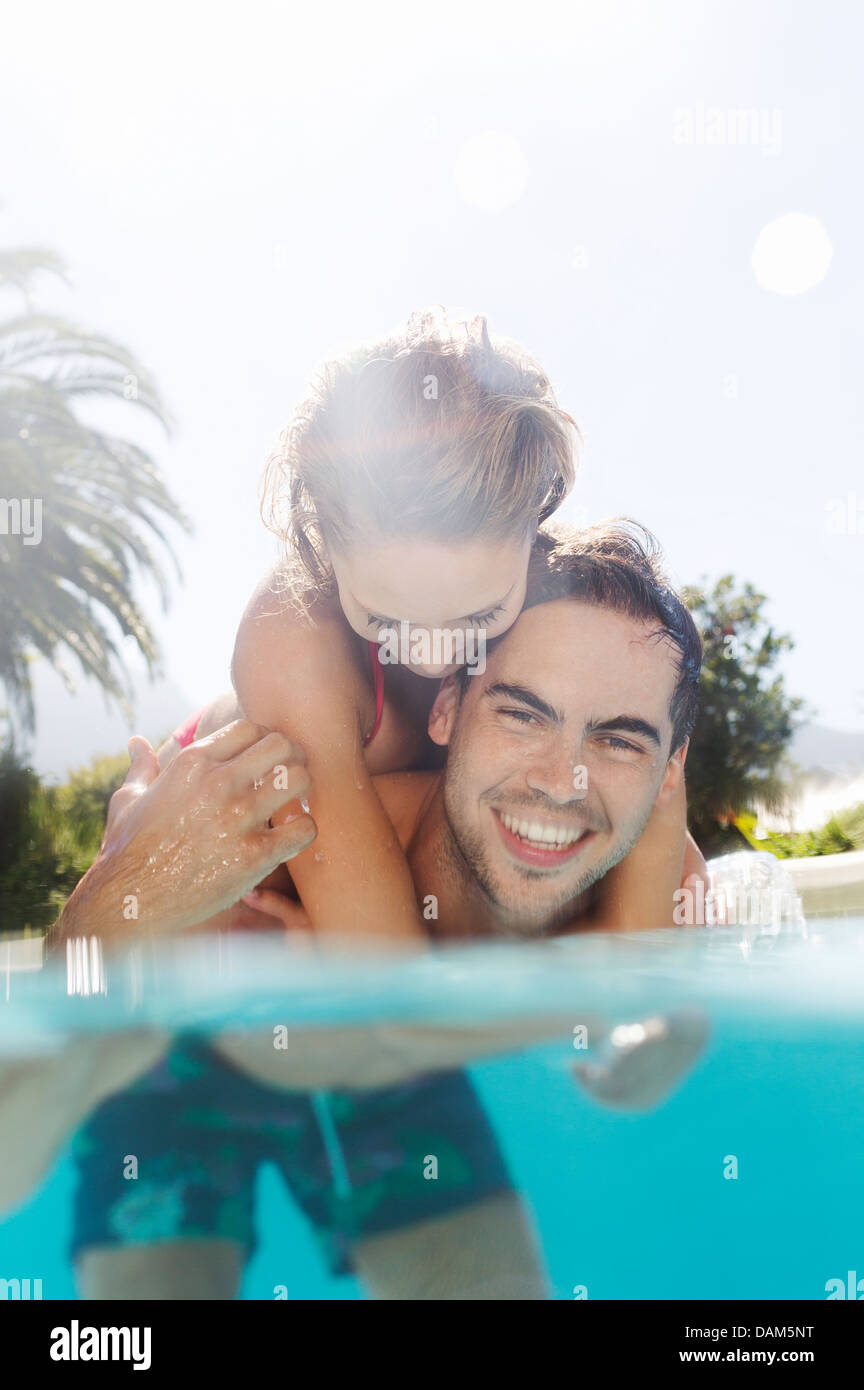 Couple playing in swimming pool - Stock Image