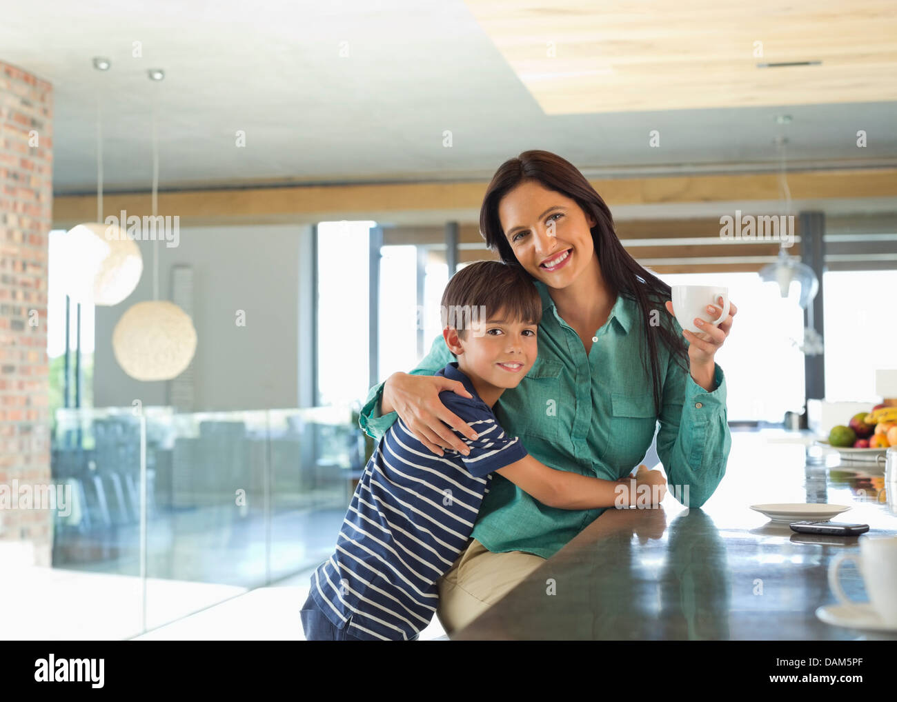 Mother and son smiling in kitchen - Stock Image