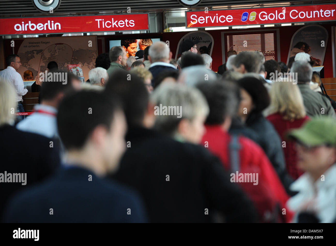 Passengers queue at a flight desk of Air Berlin at the airport in Hamburg, Germany, 25 May 2011. An ash cloud of - Stock Image