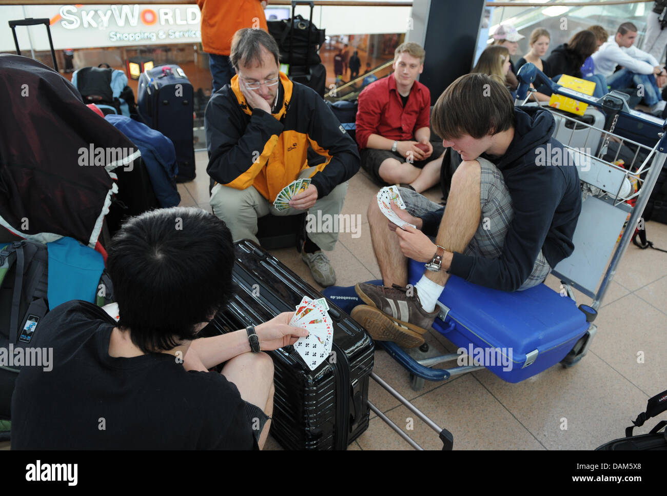 Pupils of the twelfth grade from Eckernfoerde play cards at the airport in Hamburg, due to their delayed flight - Stock Image