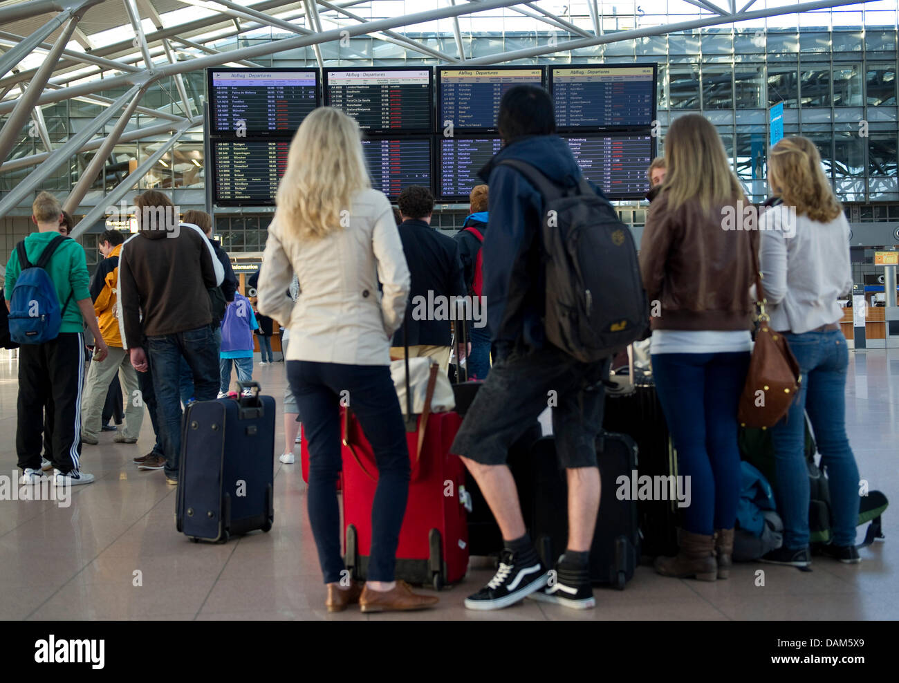Passengers seek information in front of a destination board at the airport in Hamburg, Germany, 25 May 2011. An - Stock Image
