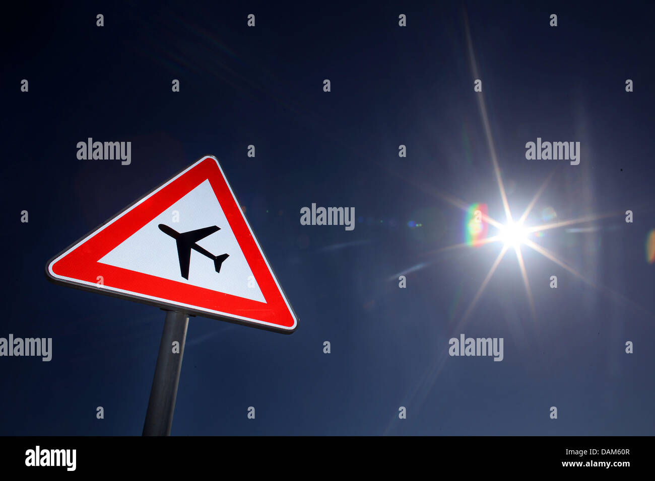 A traffic sign pointing to possible airplanes approaching or taking off is pictured at a street between Cologne - Stock Image