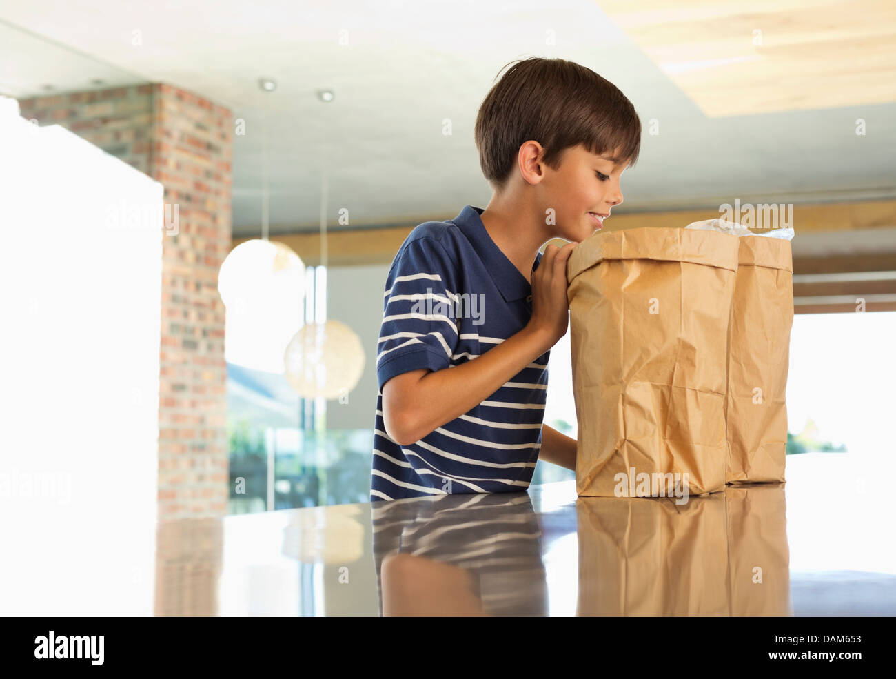 Boy looking through paper bag in kitchen - Stock Image