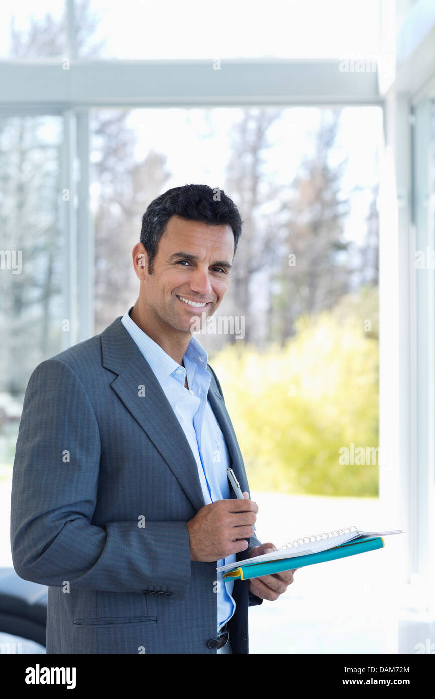 Businessman reading papers in office - Stock Image