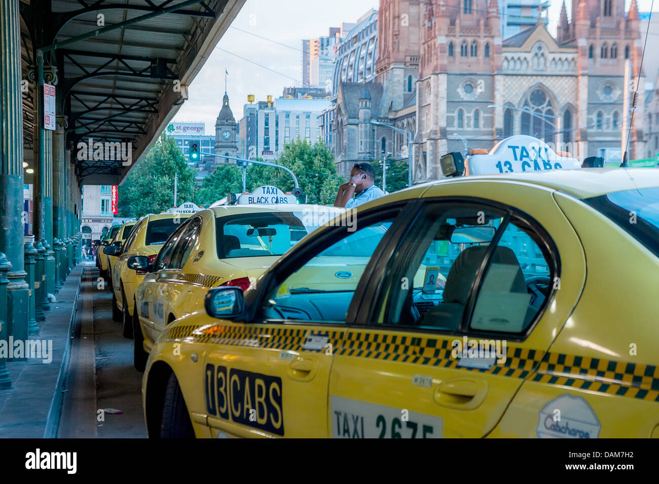 Taxi cabs line up at Flinders Street railway Station in downtown Melbourne, waiting for passengers. - Stock Image