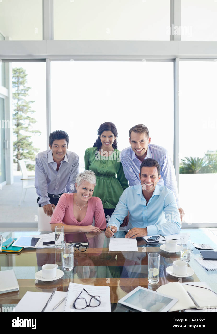 Business people smiling in meeting - Stock Image