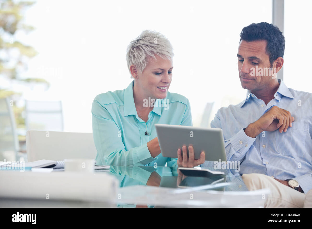 Business people using tablet computer on sofa - Stock Image