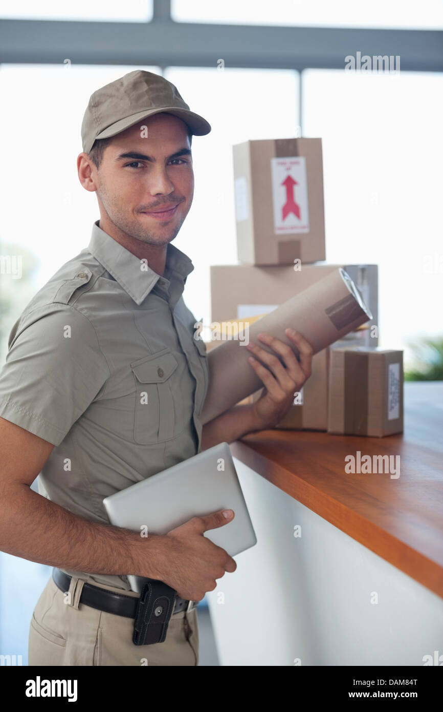 Delivery boy with packages in office - Stock Image