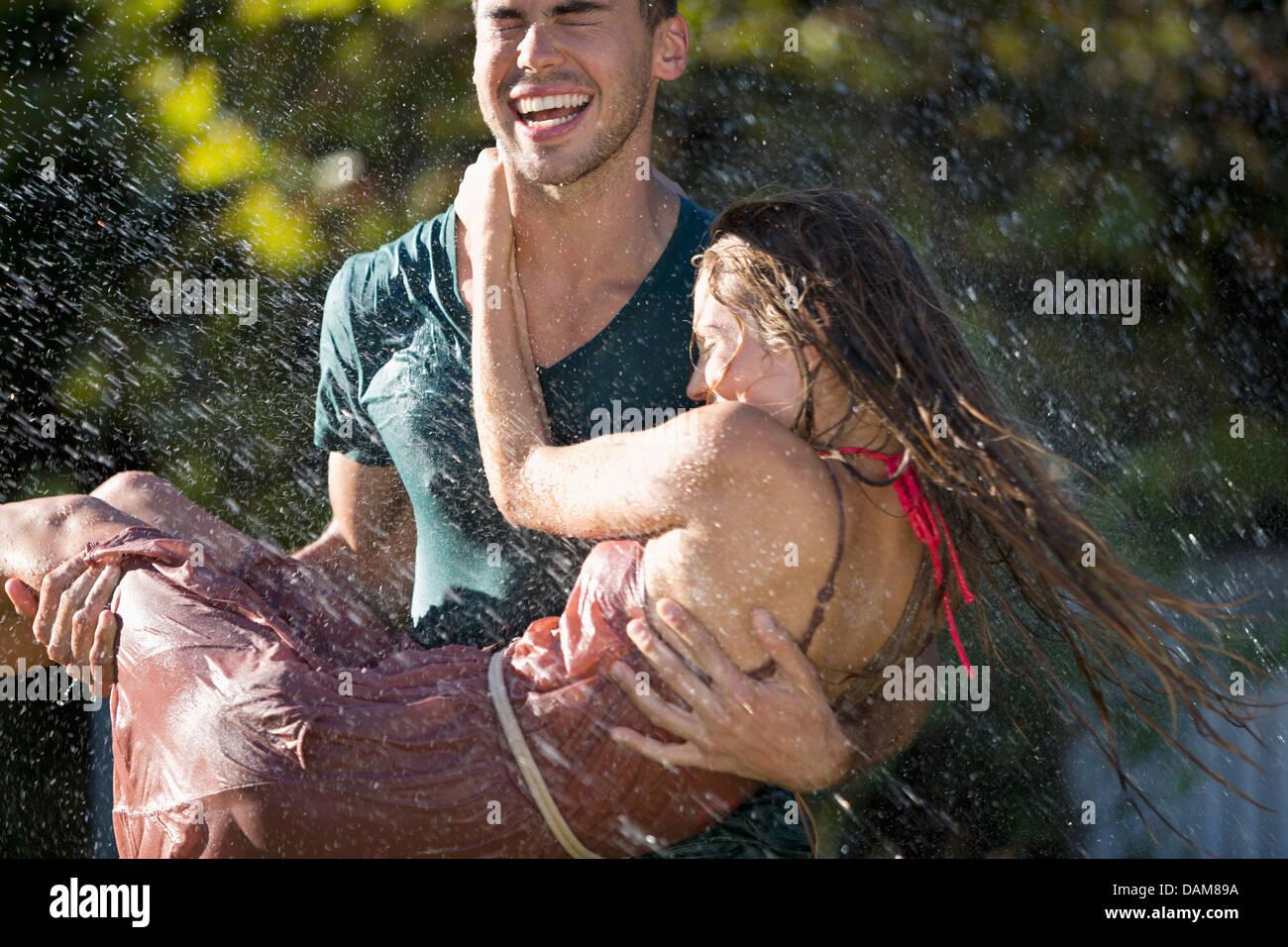 Couple playing in sprinkler in backyard - Stock Image