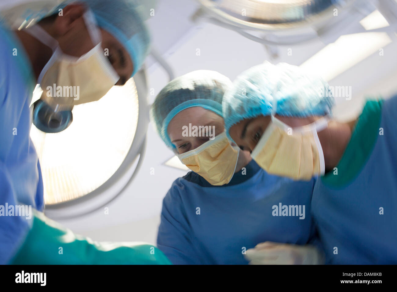 Surgeons bent over patient in operating room - Stock Image