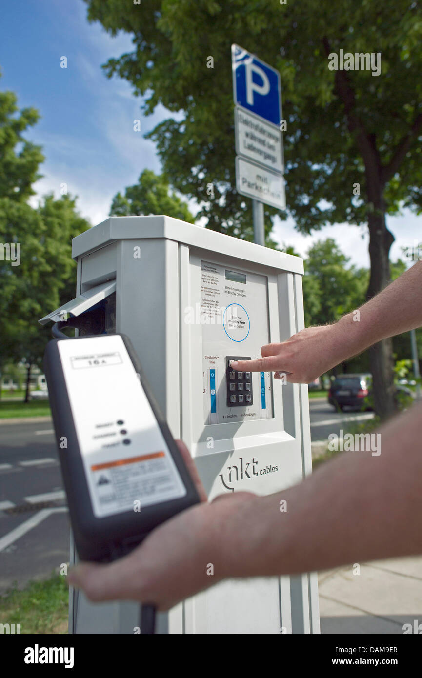 A man uses an electric filling station for an electric car from DREWAG Public Utilities GmbH in Dresden,Germany, - Stock Image