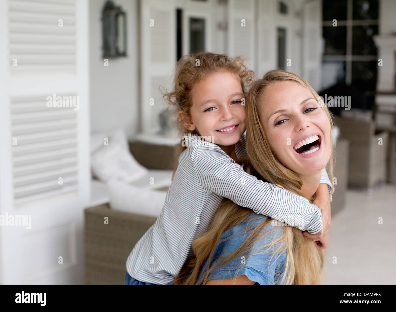 Mother and daughter playing on porch - Stock Image