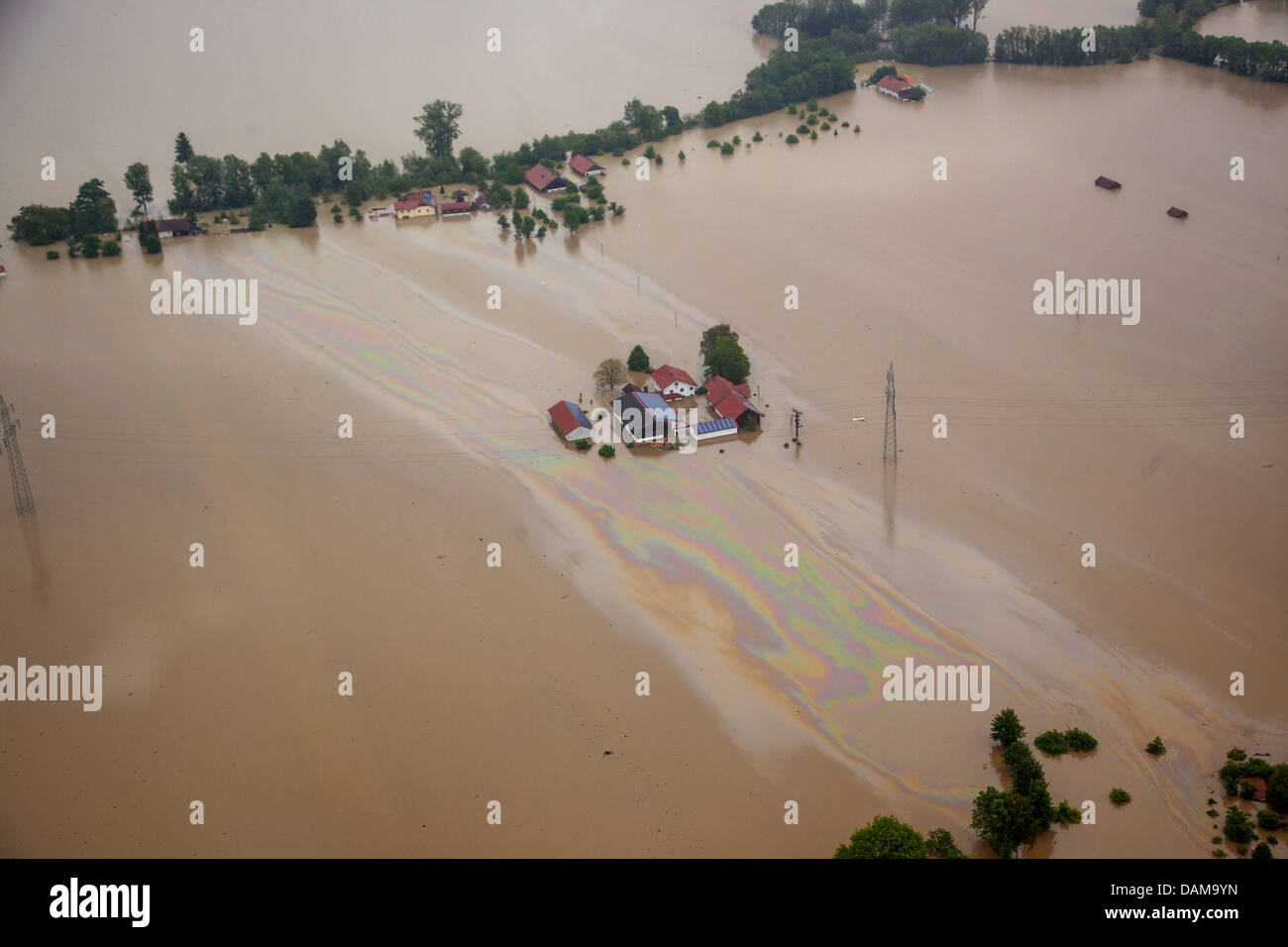 farmhouses and large oil layer on river Inn during the flood in June 2013, Germany, Bavaria Stock Photo