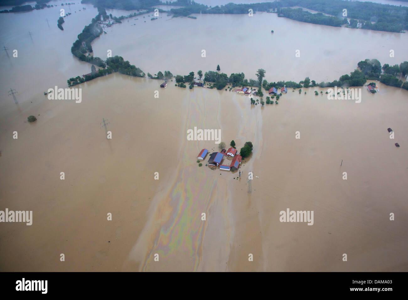 farmhouses and large oil layer on river Inn during the flood in June 2013, Germany, Bavaria, Schaerding - Stock Image