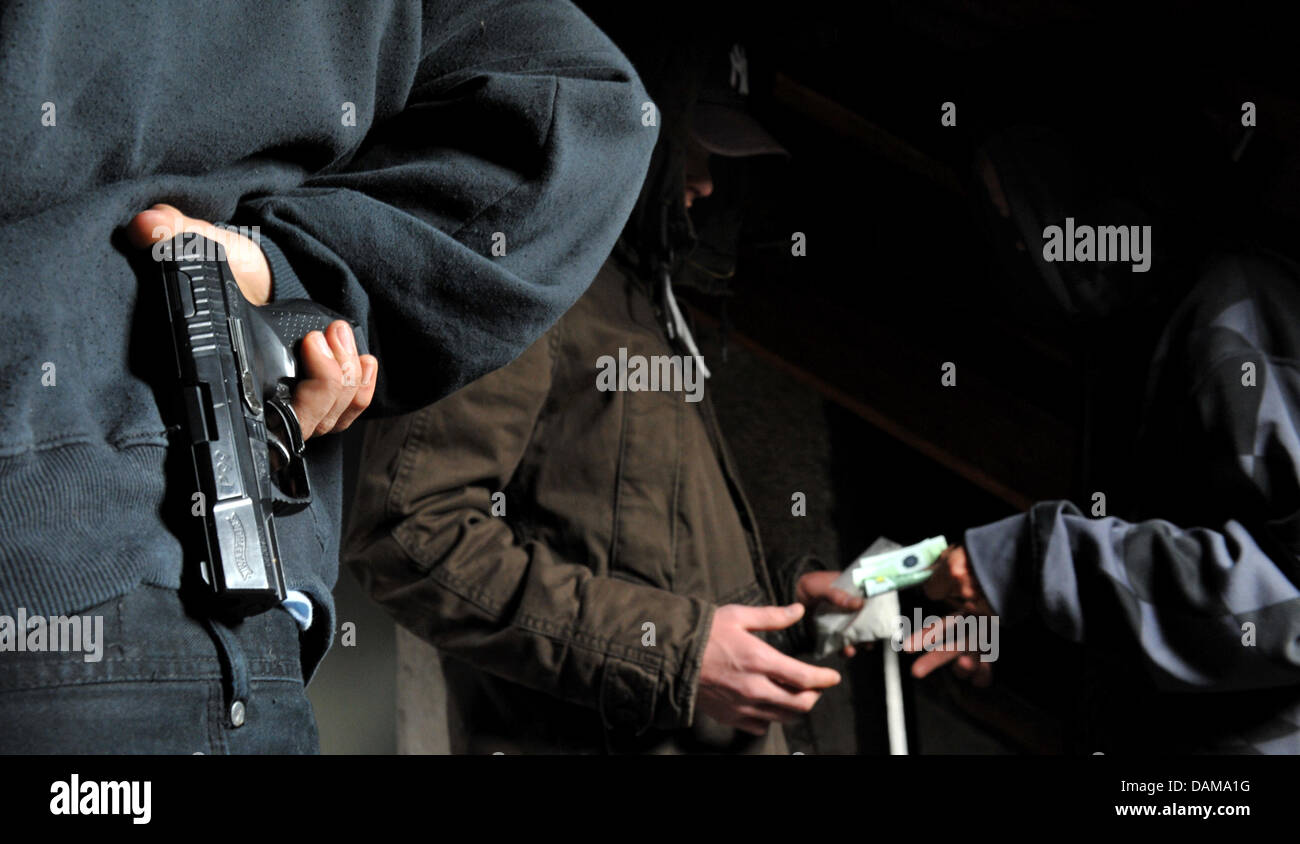ILLUSTRATION  - The replicated scenario shows a drug dealer and a reproduced gun, pictured in Munich, Germany, - Stock Image