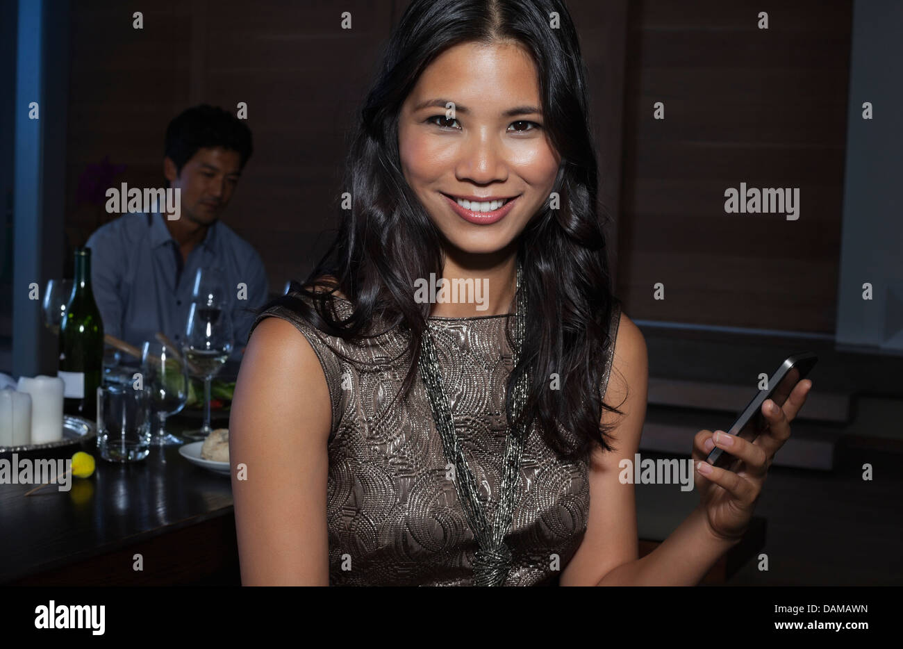 Woman using cell phone at party - Stock Image