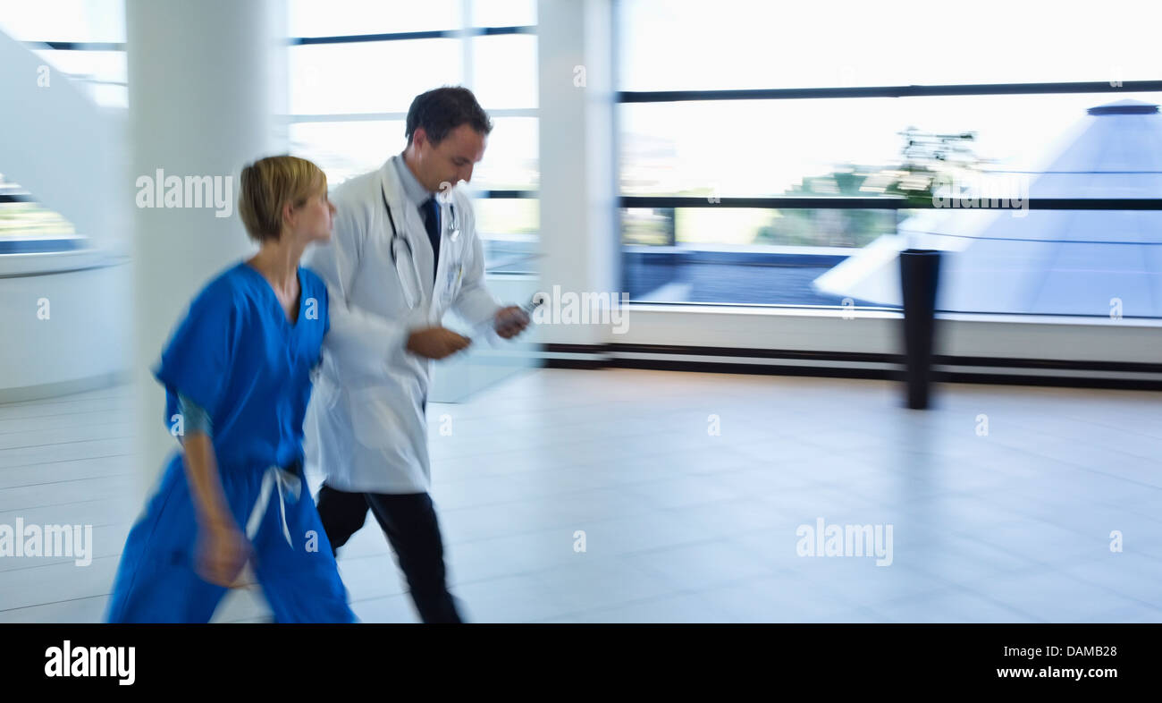 Doctor and nurse talking in hospital hallway Stock Photo