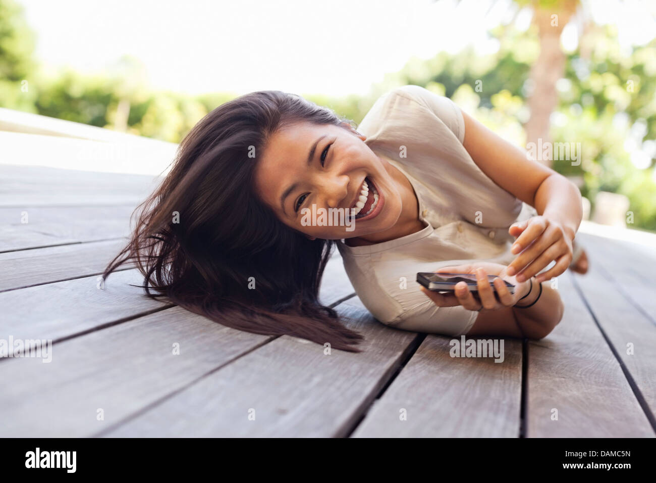 Woman using cell phone on wooden deck Stock Photo