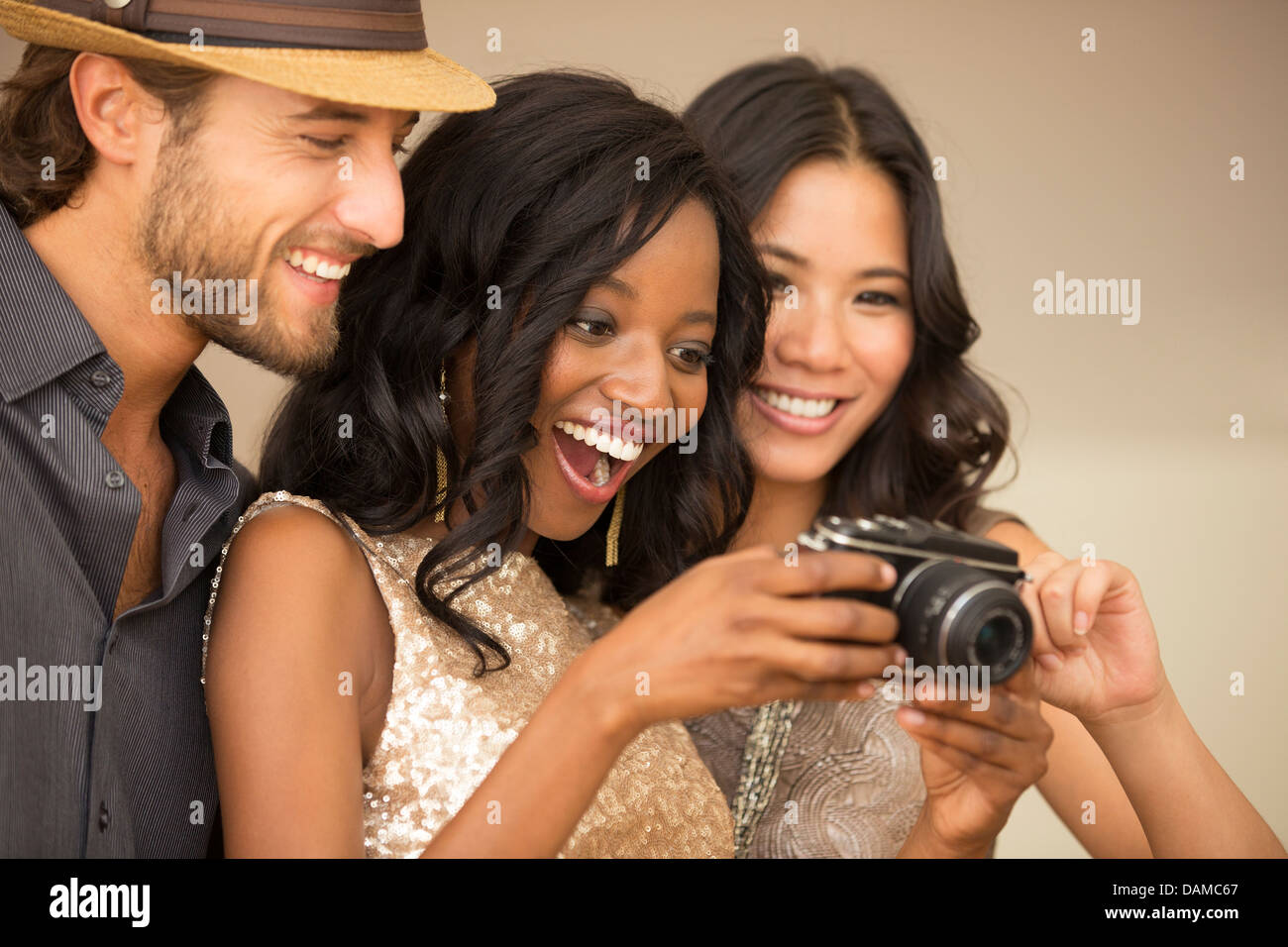 Friends using camera at party - Stock Image