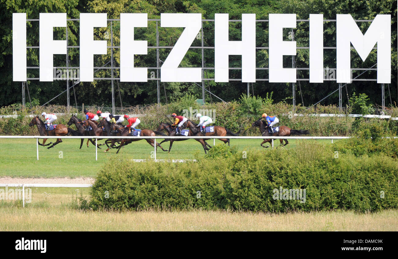 A group of horse riders race across the horse race track Iffezheim on the last day of the so-called Spring Meeting - Stock Image