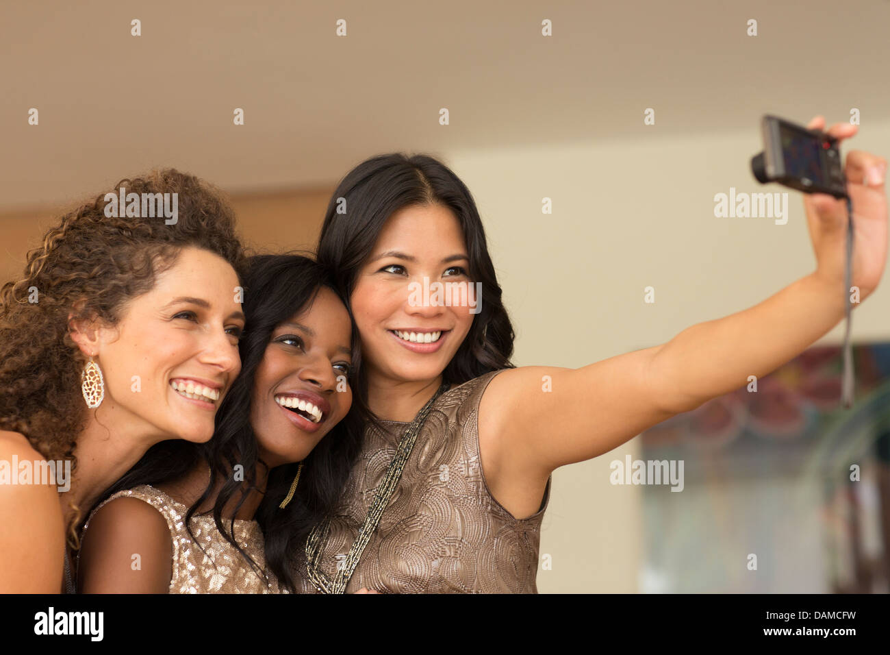 Women taking picture together indoors - Stock Image