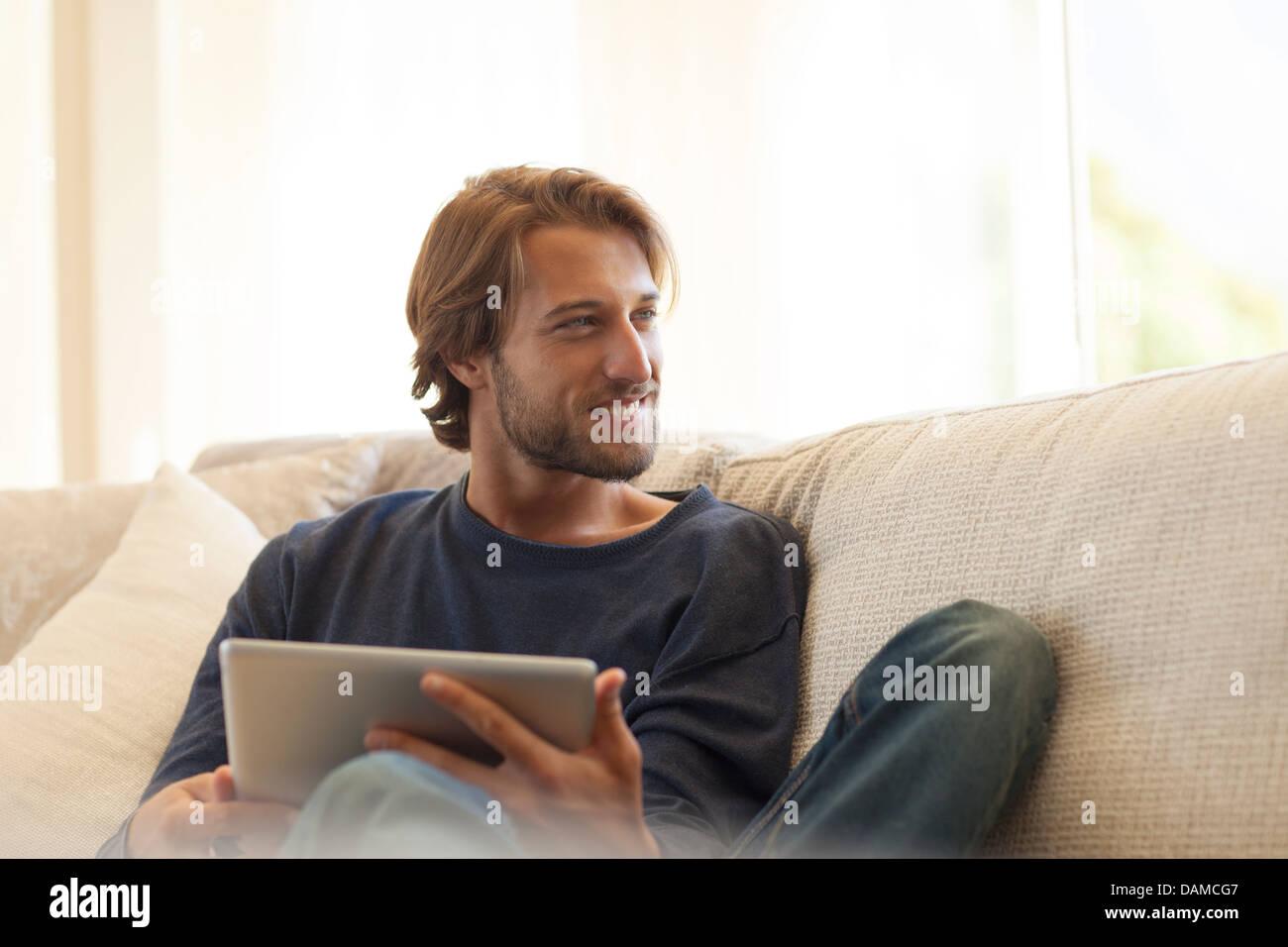Man using tablet computer on sofa - Stock Image