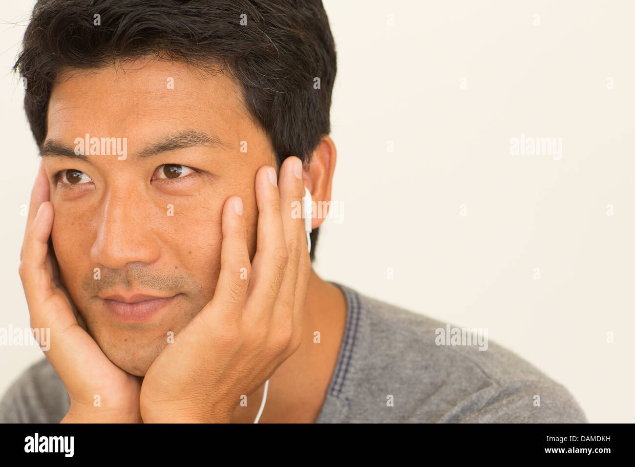 Man resting chin in hands - Stock Image