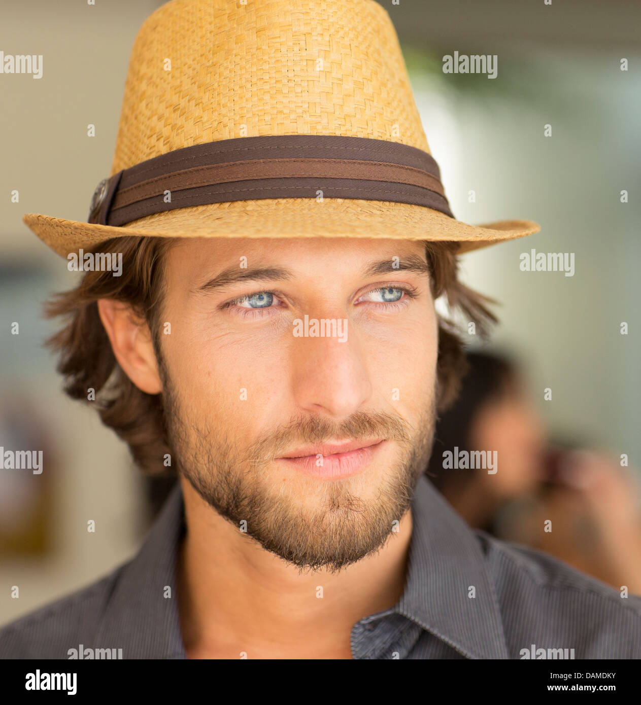Smiling man wearing straw hat - Stock Image