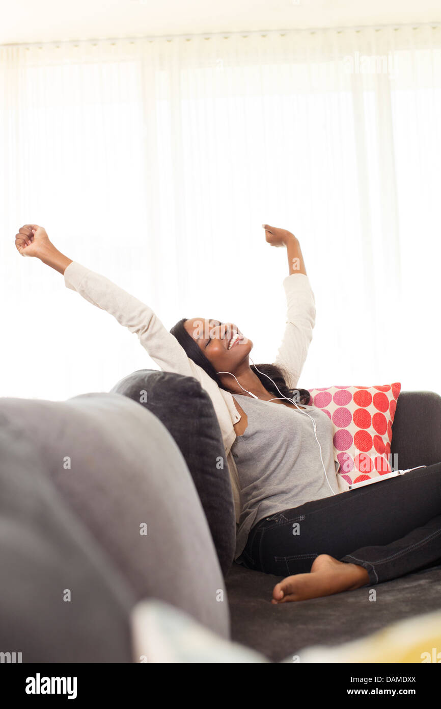 Woman stretching on sofa - Stock Image