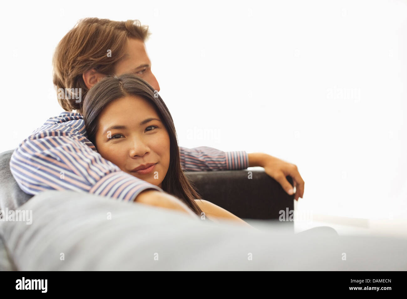 Smiling couple relaxing on sofa - Stock Image