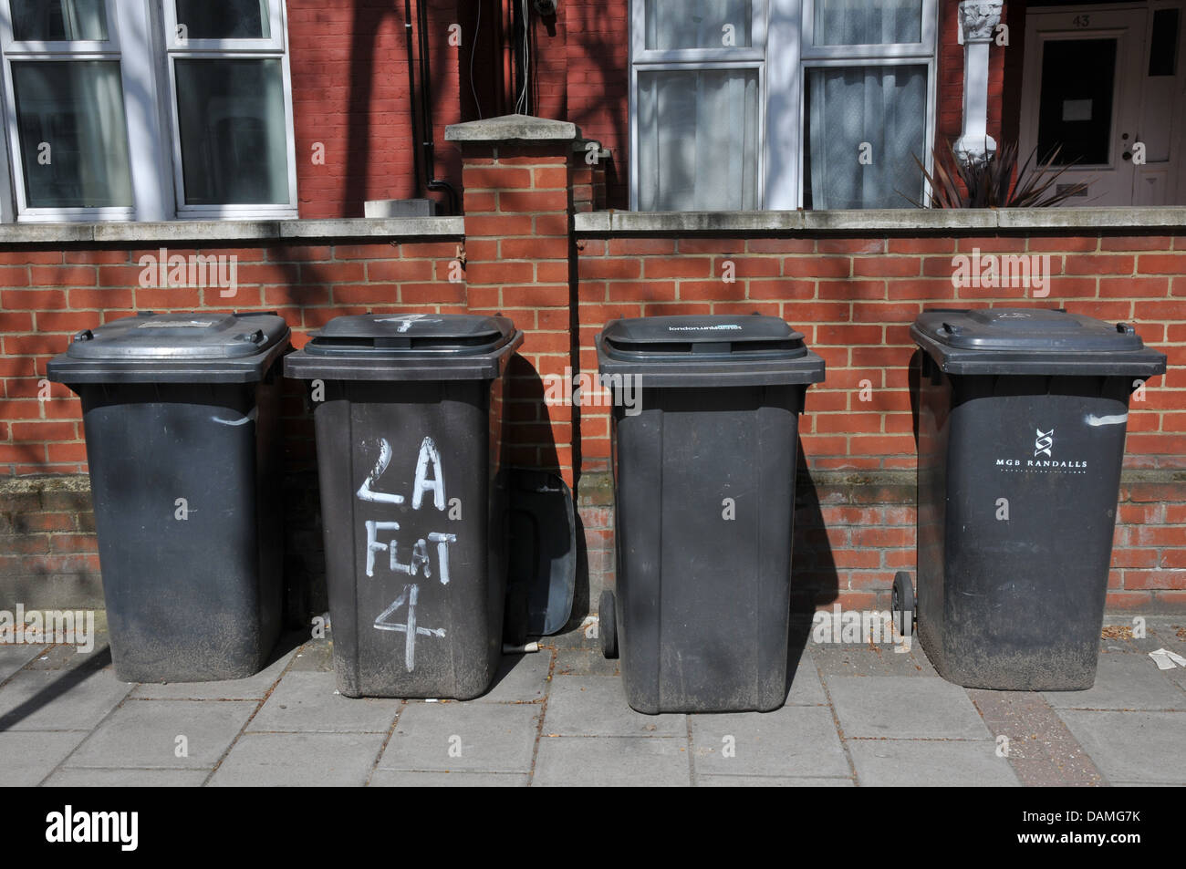 Four black rubbish bins, lined up on street, London - Stock Image
