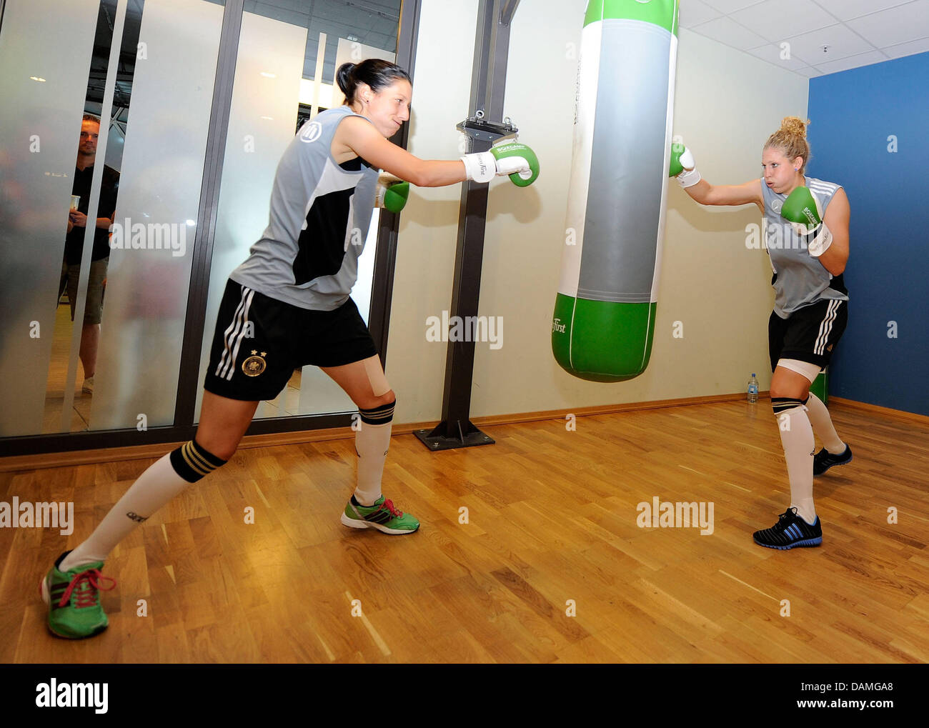 Verena Faisst (L) and Kim Kulig (R) of the German national soccer team punch a bag during a training session at - Stock Image