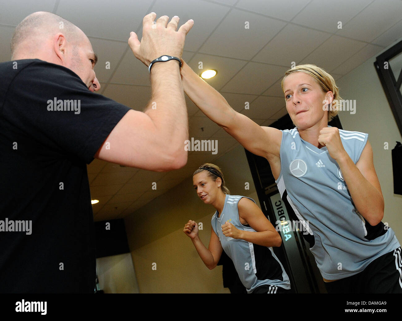 Saskia Bartusiak (R) of the German national soccer team boxes with a trainer during a training session at a Fitness - Stock Image