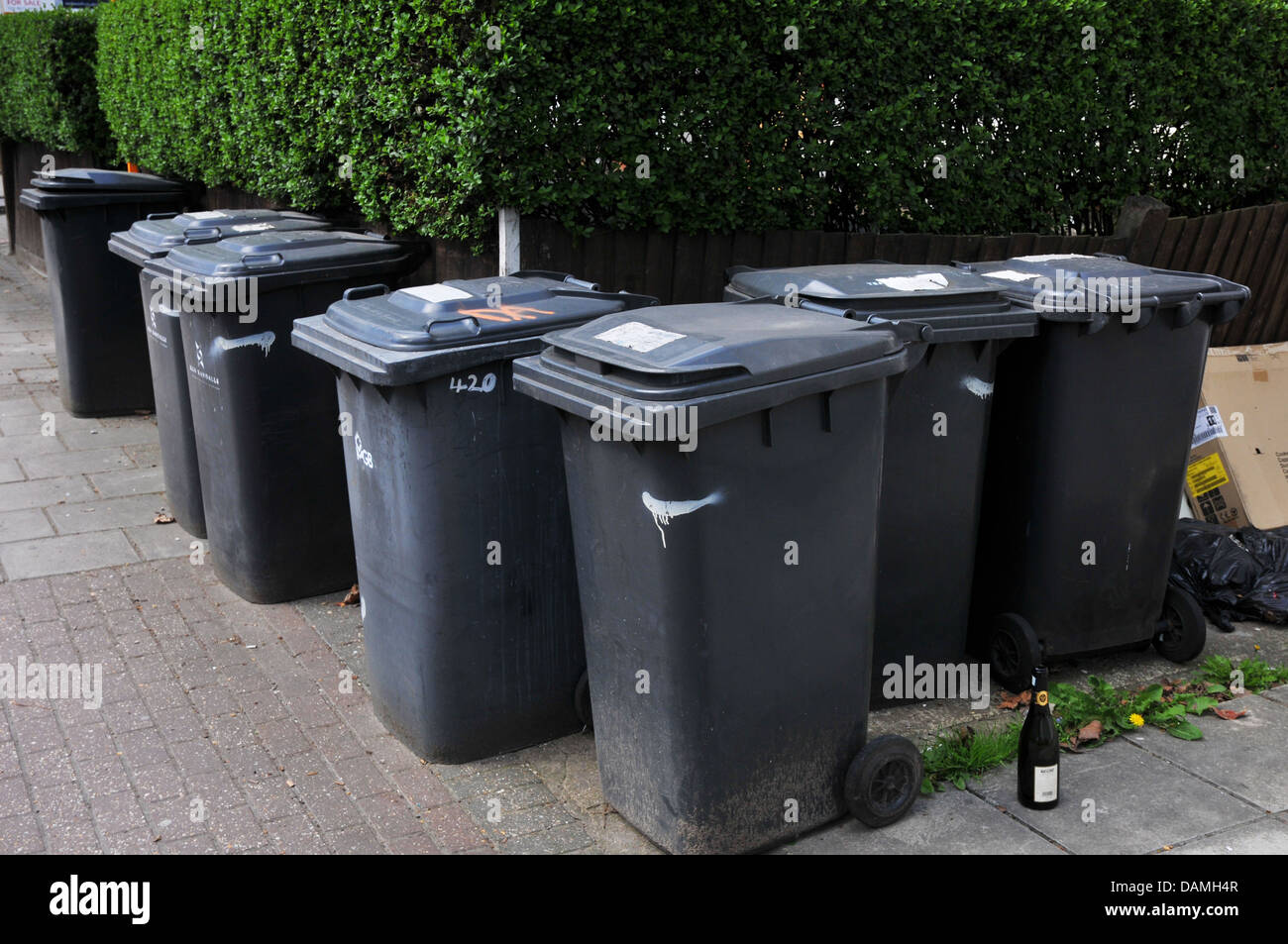 Group of black rubbish bins together, in street, awaiting collection, London - Stock Image