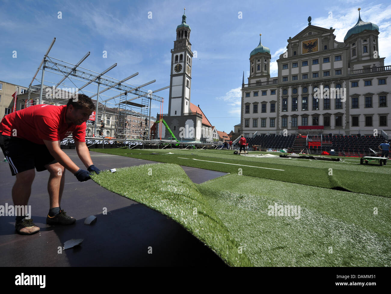 Workers lay out artificial grass in front of the city hall at the