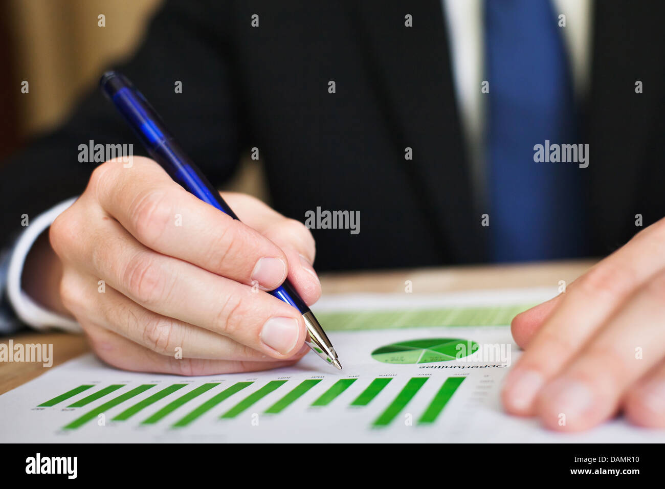 Businessman analyzes a successful sustainable development on a bar chart - Stock Image