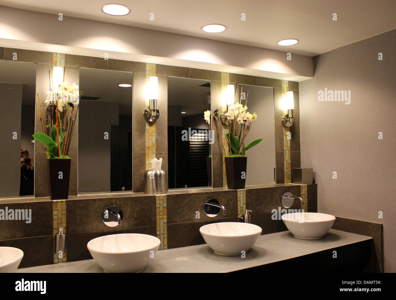 Ultra Chic Bathroom With Fancy Sinks,mirrors And Flower Arrangements,subtle  Lighting Overhead In Upscale City Hotel.