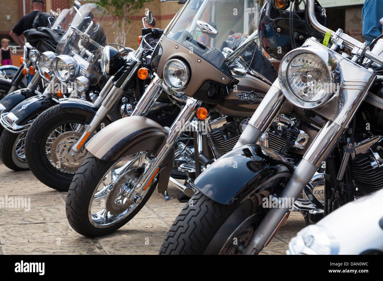 row of headlamps and front forks of Harley Davidson motorcycles - Stock Image