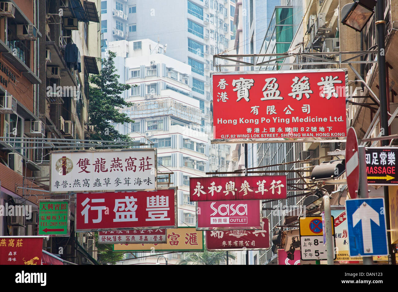 One of the countless busy streets in Hong Kong showing the signs that hang over head - Stock Image