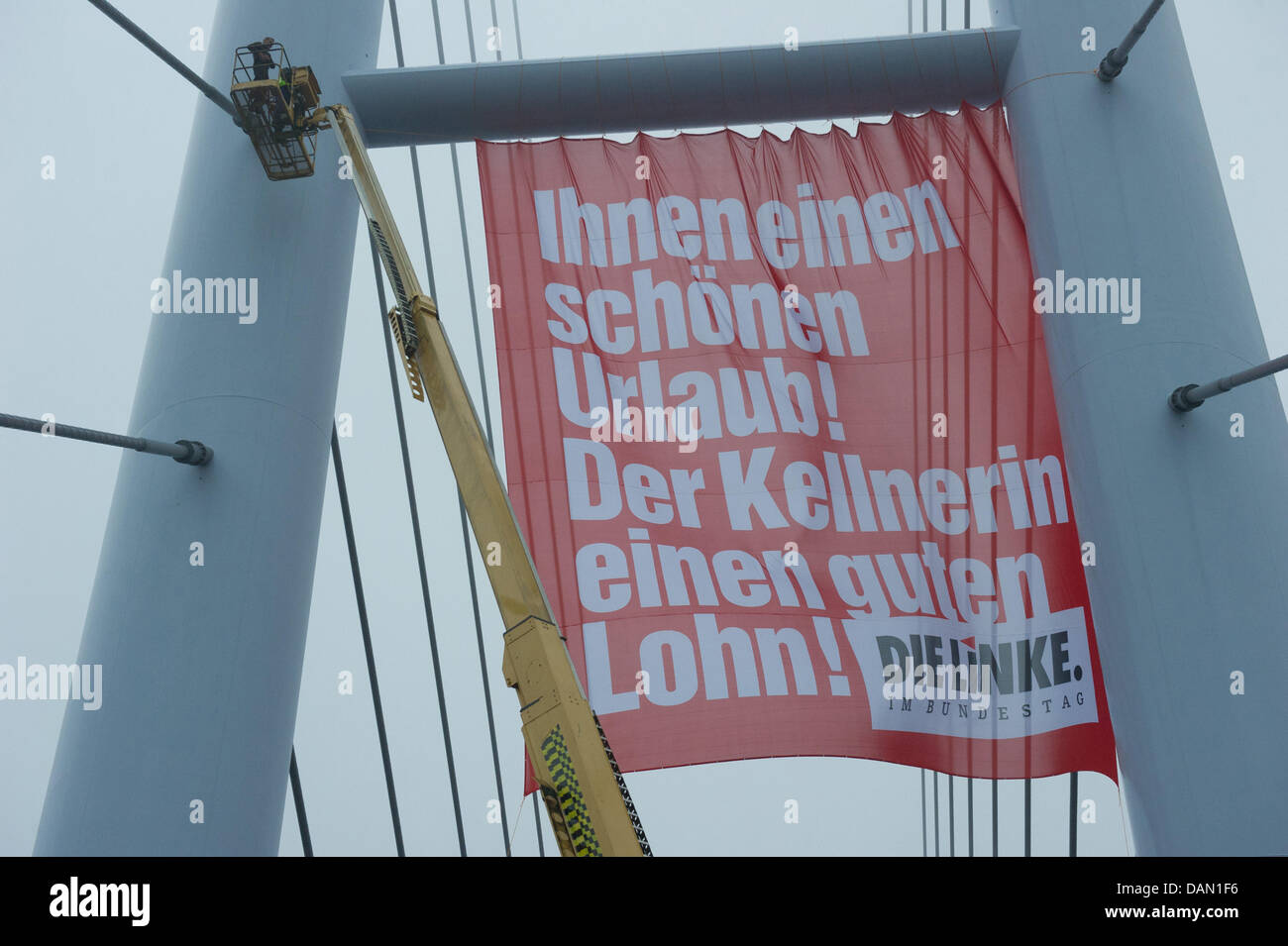 Workers hang a banner from 'Die Linke' (The Left) political party on the Ruegen Bridge in Stralsund, Germany, - Stock Image