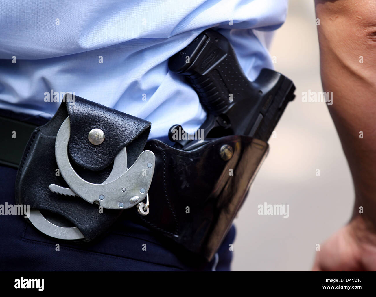 A policeman wears handcuffs and a weapon during a visit to the Kreuzgasse School in Cologne, Germany, 28June - Stock Image