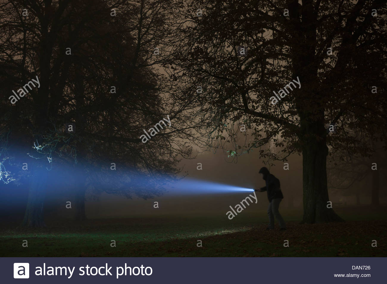 Germany, Munich, Young man with torch in foggy night Stock Photo
