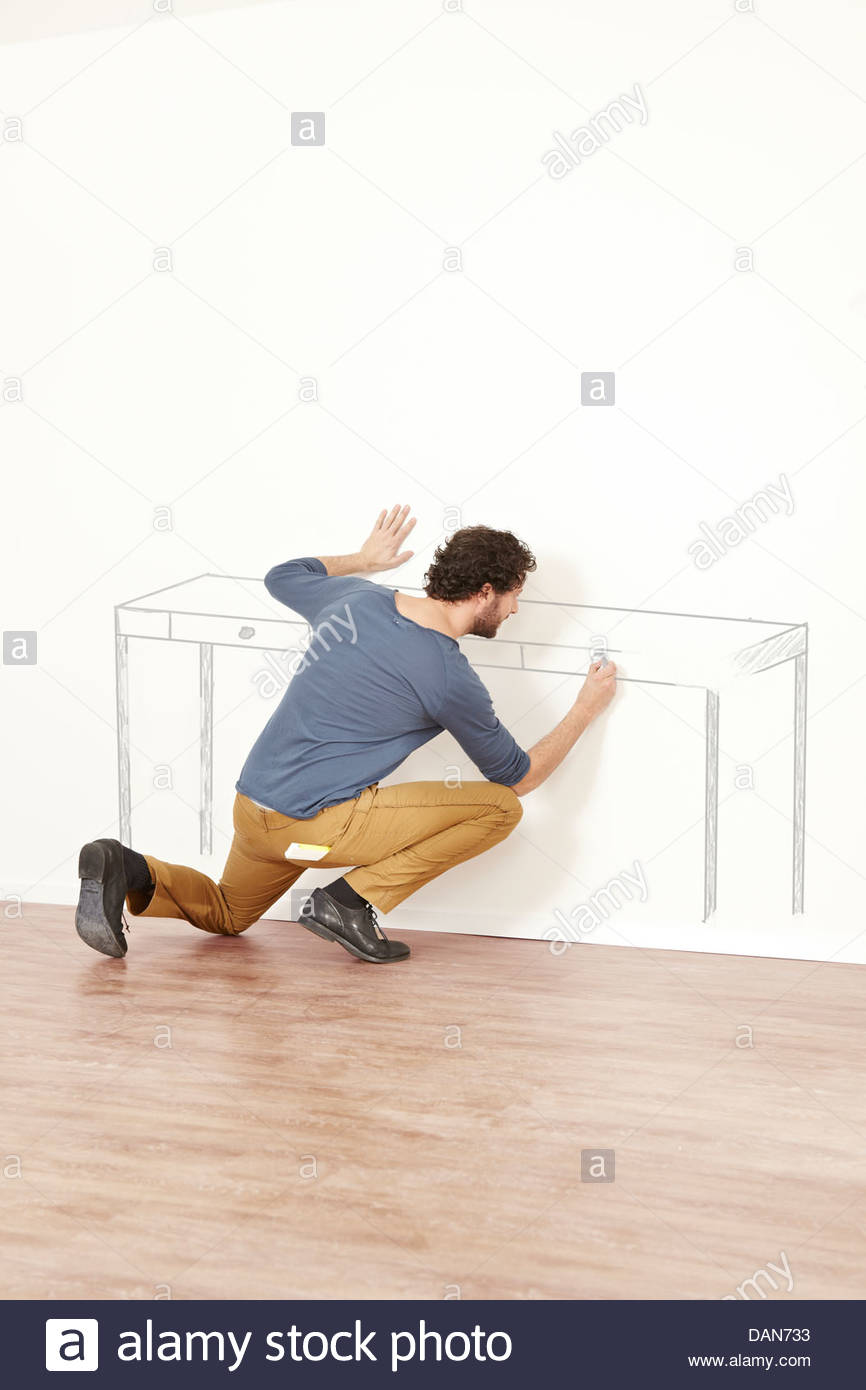 Man creating outline of table on wall - Stock Image