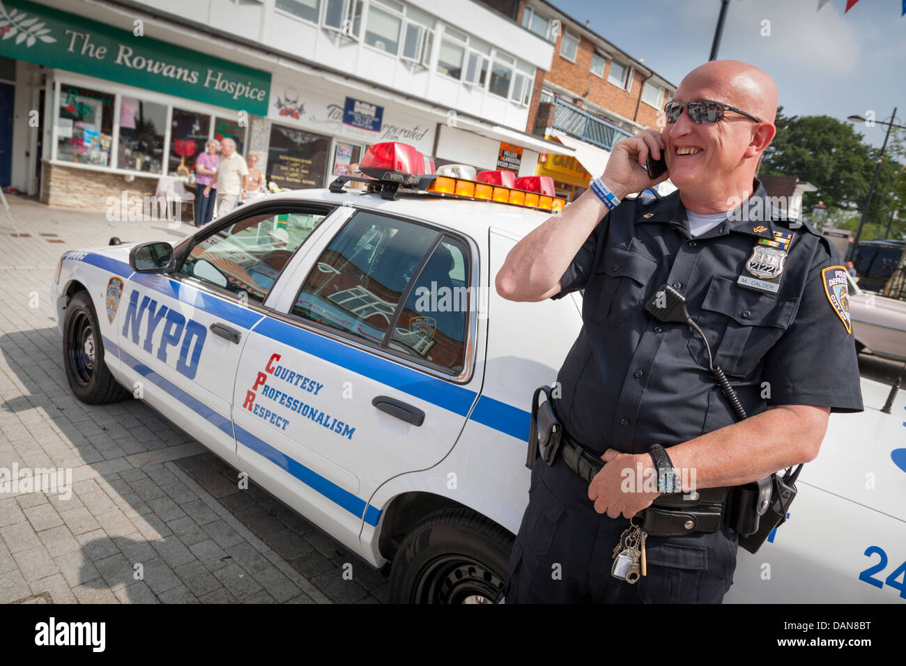 enthusiast dressed as police man leaning against NYPD classic car at show - Stock Image